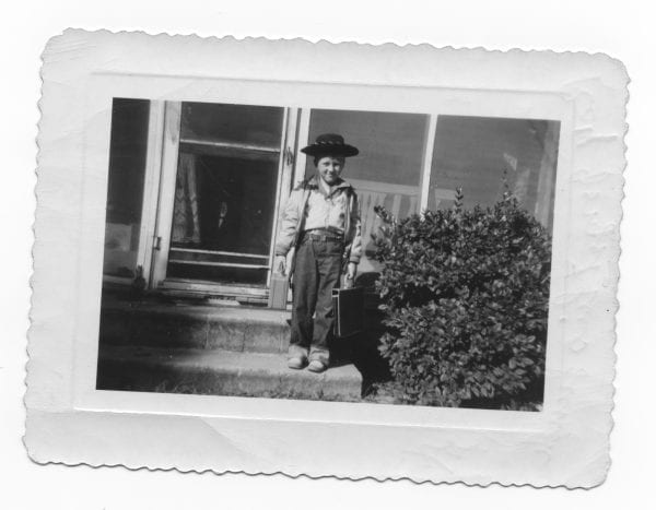 Studious Cowboy Ray, about age 6, circa 1950, on the way to school. House in background was built by my grandfather by hand during the Great Depression. This semi-rural area of North Carolina has lots of pine trees, sand, sand spurs, and little critters called chiggers (they are not nice pets). Behind the house was a barn, a mule, a cow, some chickens, and the outhouse. Yep, in the winter I had cold buns back then.